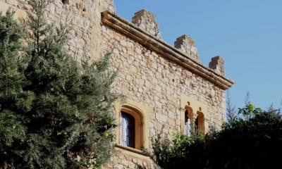 Part de la façana principal on s'observen dues de les obertures i el coronament emmerletat del castell (2015)