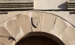 Escut de la dovella central del portal, on s'observen, esculpits en la pedra, l'acrònim Jesús Home Salvador i l'any de la refor- ma de la casa (2015)