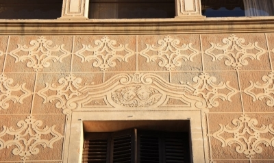 Detall de l'esgrafiat de la façana i dels emmarcaments de les obertures decorades amb un parell d'angelets (2015)