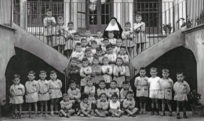 Grup de nens a l'escala del pati de l'escola coneguda com a Col·legi Pensionat de Religioses de la Divina Pastora de Piera (dècada de 1960)