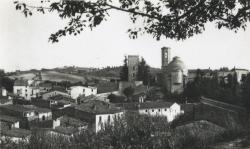 Vista del barri del Raval de Piera. Sota el castell i l'església s'hi observa l'antiga escola, d'on sobresurt el campanar de cadire- ta (dècada de 1950)