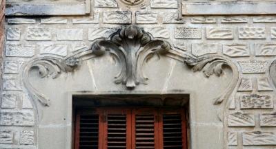 Detall de l'emmarcat floral de les obertures que trenca amb l'acabat simulant carreus de la resta de la façana (2015)